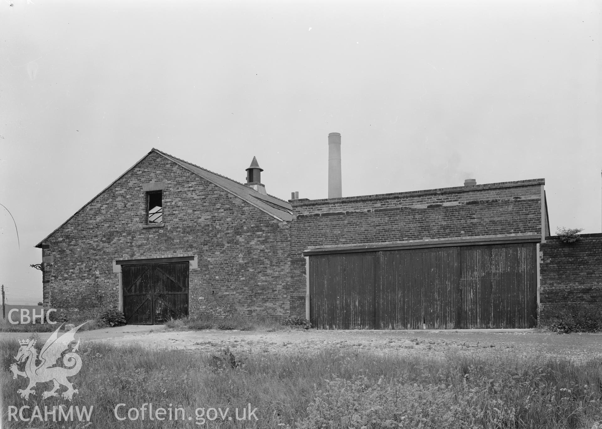 D.O.E photograph of Flint Gaol - south east elevation of drill hall and garages, from east. In castle outer ward (since removed).