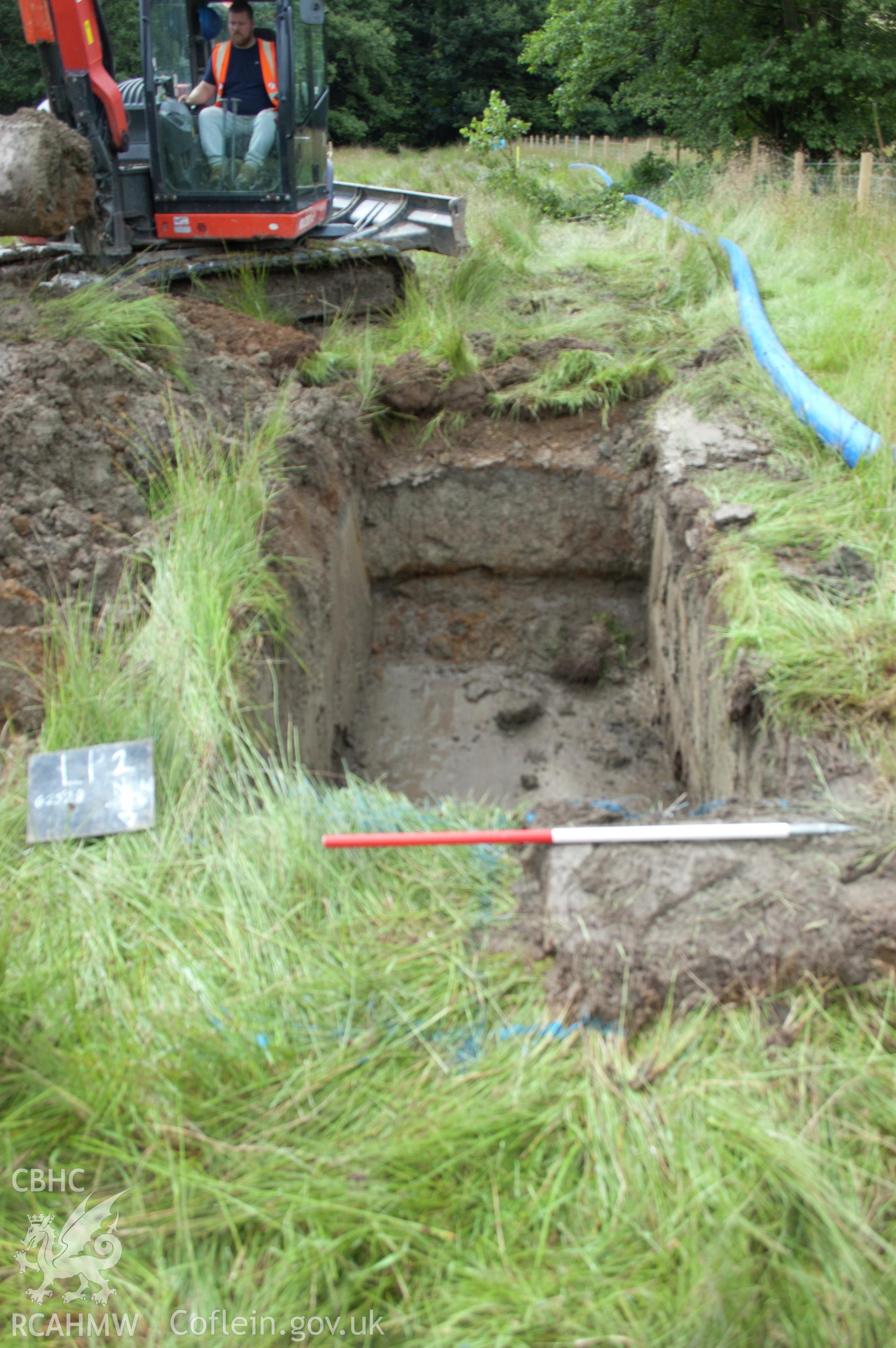 Digital photograph of view from north of launch pit 2 post-excavation showing grey clay fill. Photographed during Gwynedd Archaeological Trust's archaeological watching brief of water main renewal in Dolgellau on 28th July 2017. Project no. G2528.