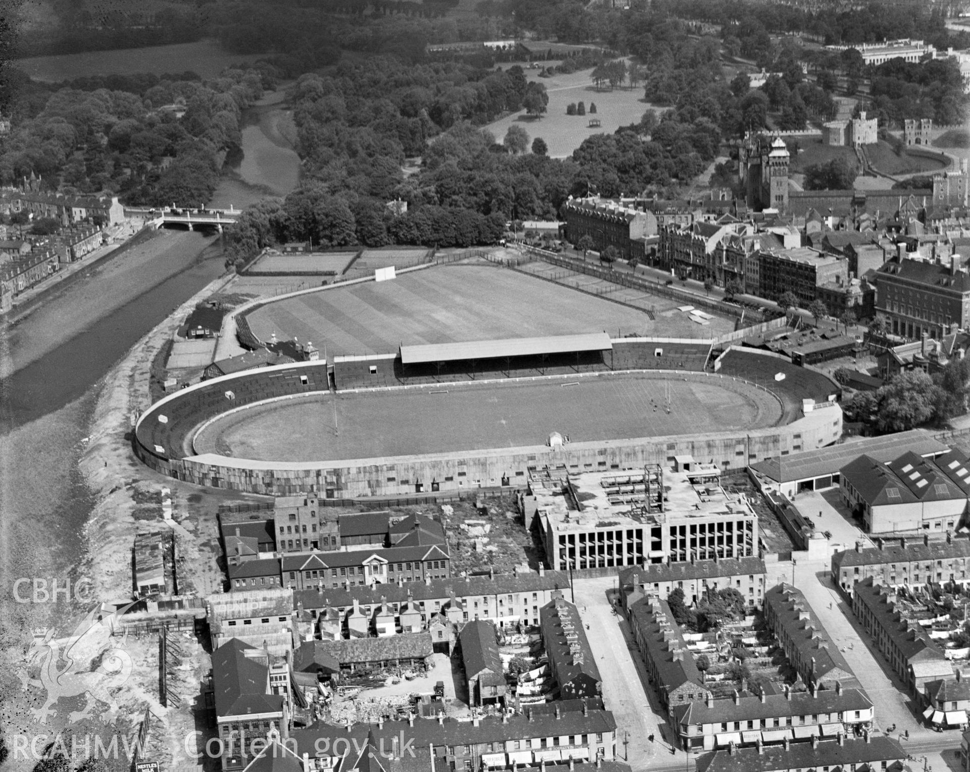 Digital copy of a black and white, oblique aerial photograph of Cardiff Arms Park, Cardiff. The photograph shows the view from the South East, showing Temperance Town in the foreground before its demolition by the Cardiff Corporation in 1937.