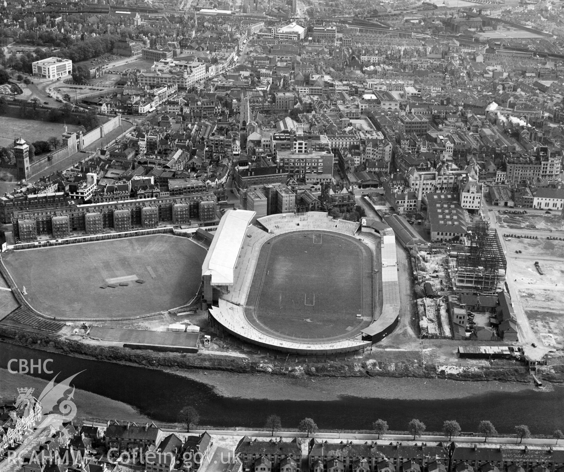 Digital copy of a black and white, oblique aerial photograph of Cardiff Arms Park, Cardiff. The photograph shows a view from the West following the completion of the North Stand. On the right hand side of the photograph it iss possible to see Empire House, a telephone exchange, under construction on the site of the Temperance Town which was demolished by the Cardiff Corporation in 1937.