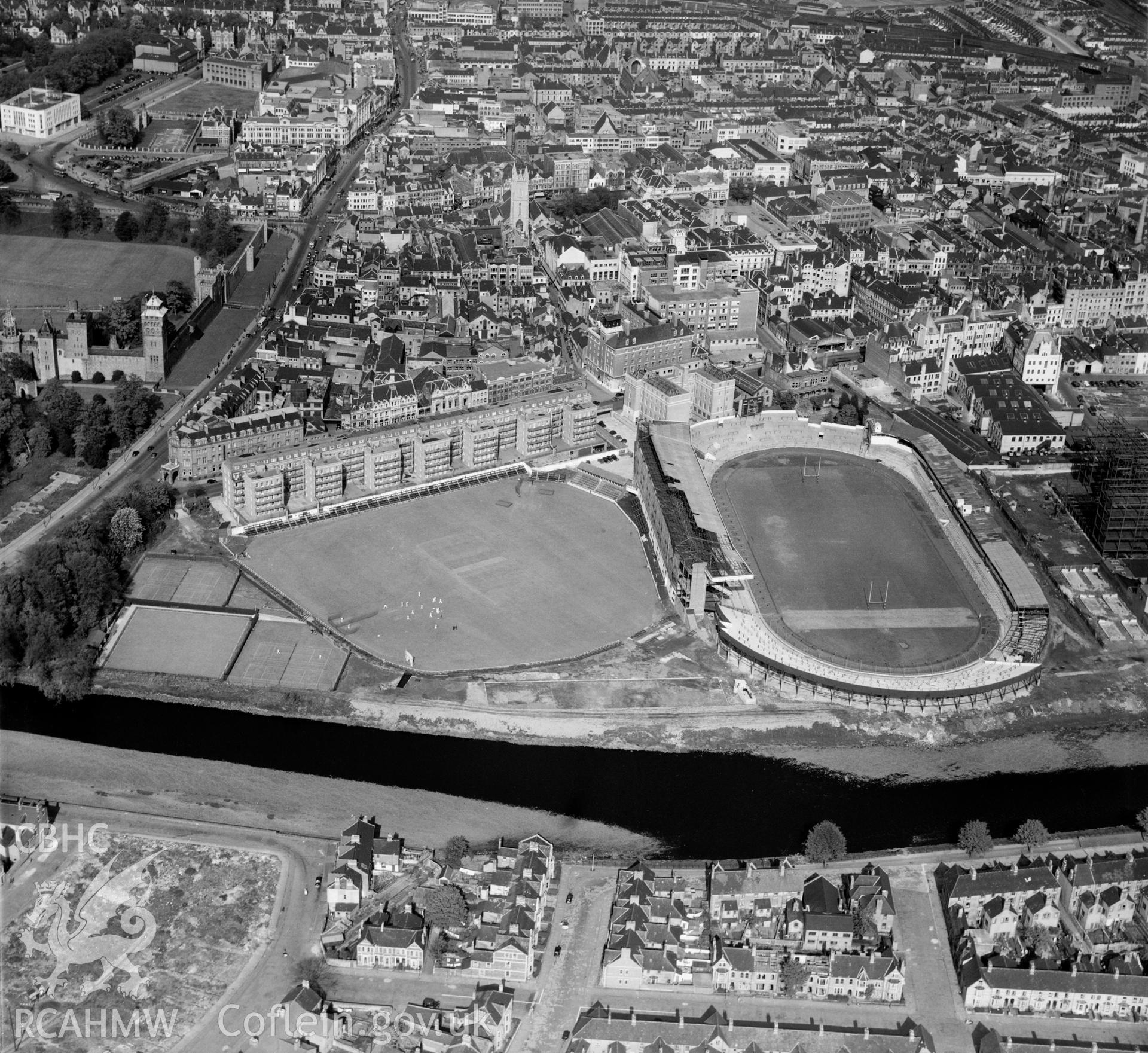 Digital copy of a black and white, oblique aerial photograph of Cardiff Arms Park. The photograph shows a view from the West showing the new North stand under construction.