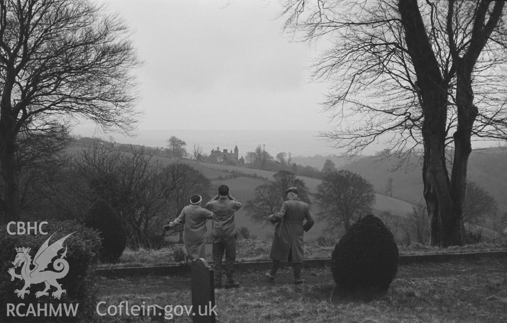 Black and White photograph showing distant view of Bronwydd from Llangynllo churchyard, with three figures. Photographed by Arthur Chater in April 1962, from Grid Reference SN 352 439, looking south.