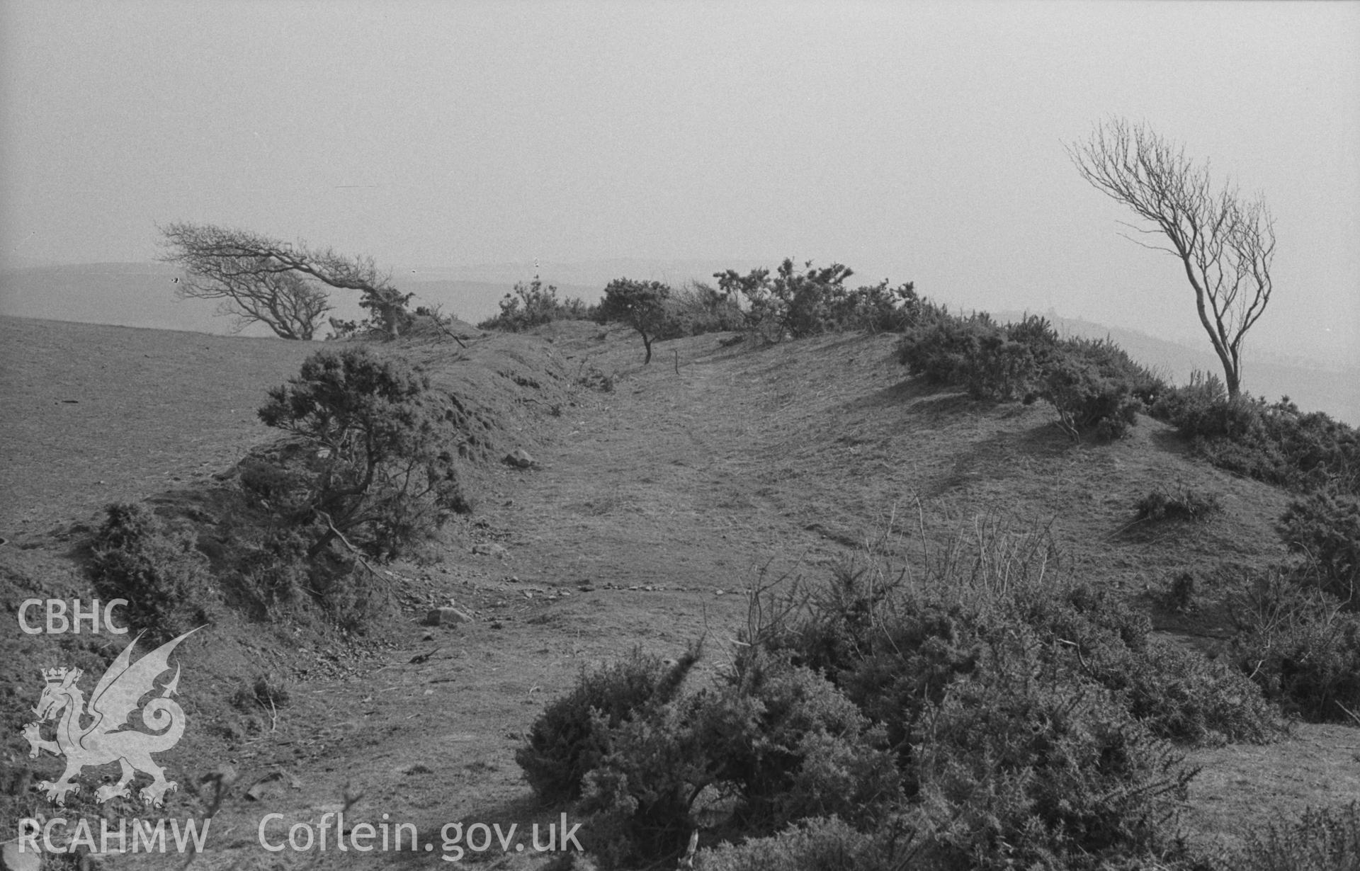 Digital copy of a black and white negative showing ramparts (and apparent entrance) at west side of Hen Gaer, Tirymynach, opposite the tumulus. Photographed in April 1963 by Arthur O. Chater from Grid Reference SN 6325 8445, looking south.